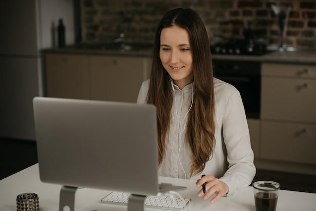 Afstandswerk. een kaukasische donkerbruine vrouw met hoofdtelefoons die ver aan haar laptop werkt. een gelukkig meisje in een wit overhemd dat zaken doet op haar thuiswerkplaats. Premium Foto