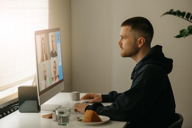 Afstandswerk. een man tijdens een videogesprek met zijn collega's op de desktopcomputer. een collega werkt intensief vanuit huis aan een online briefing. Premium Foto
