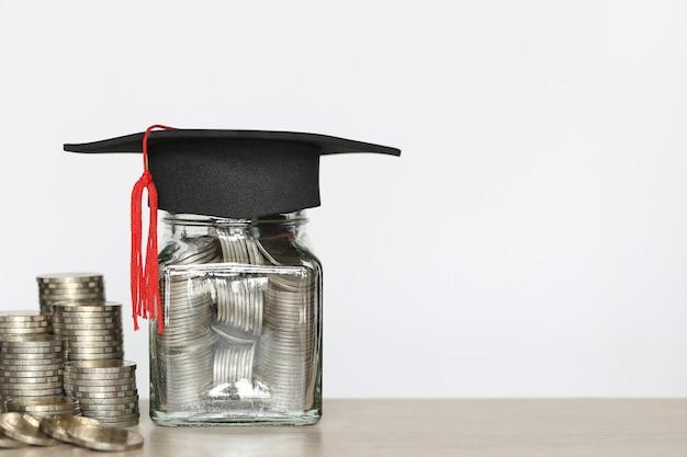 Afstudeer hoed op de glazen fles met stapel munten geld op wtite, geld te besparen voor het onderwijs Premium Foto