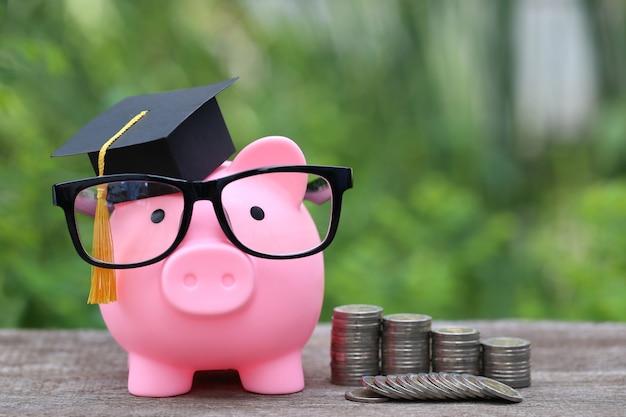 Afstudeerhoed op roze spaarvarken met stapel muntstukkengeld op aard groene ruimte Premium Foto