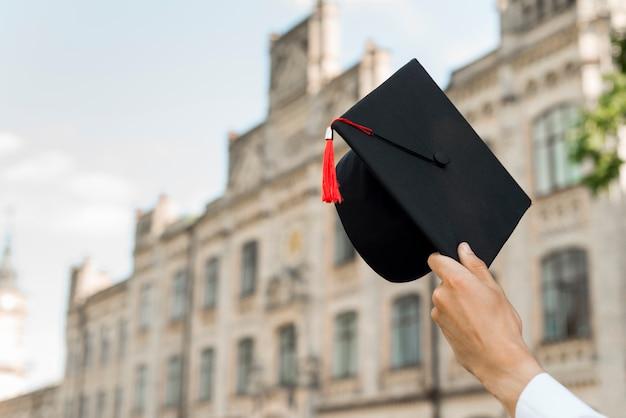 Afstuderen concept met hoed van de studentenholding Gratis Foto