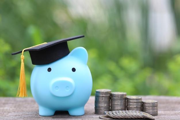 Afstuderen hoed op blauwe spaarvarken met stapel munten geld op natuur groene ruimte geld besparen voor onderwijs concept Premium Foto