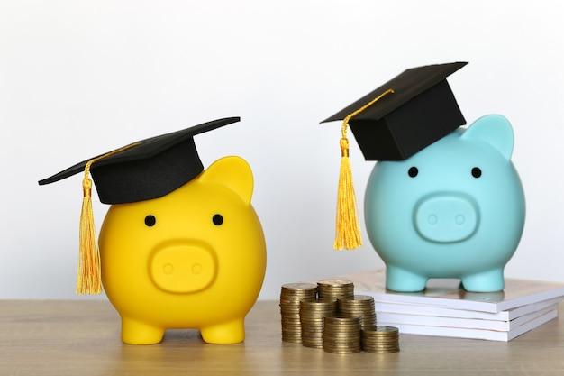 Afstuderen hoed op spaarvarken met stapel munten geld op witte achtergrond, geld besparen voor onderwijs concept Premium Foto