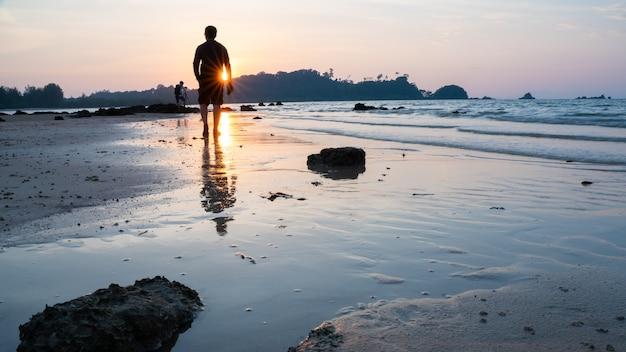 Aftekenen man lopen op zee strand bij zonsondergang Premium Foto