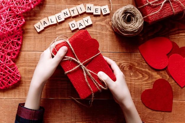 Aftelkalender voor valentijnsdag plat met handen met rode geschenk, harten en materiaal diy Premium Foto
