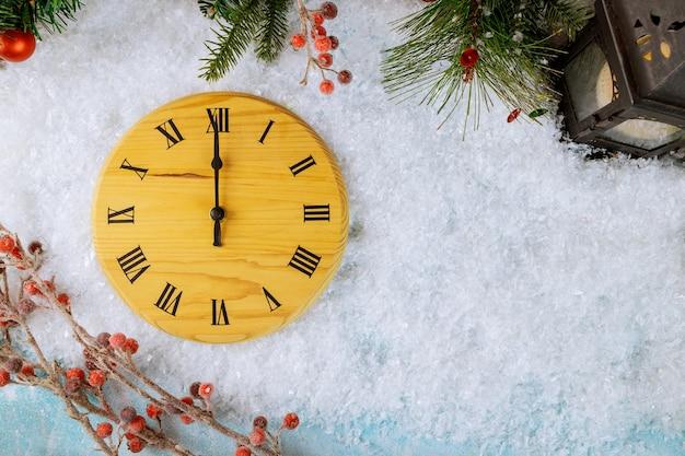 Aftellen tot middernachtsklok in houtstijl telt de laatste momenten voor nieuwjaar met dennenappel, sneeuwvlokken en balkerstmislantaarn Premium Foto