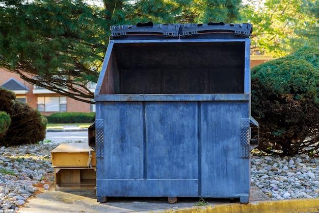 Afvalcontainers met blikjes in de buurt van woongebouwen in ecologie, milieuvervuiling. Premium Foto