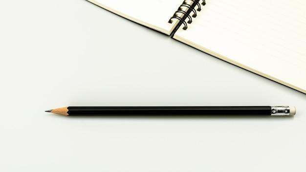 Agendaboek en een potlood op witte bureauachtergrond met exemplaarruimte Premium Foto