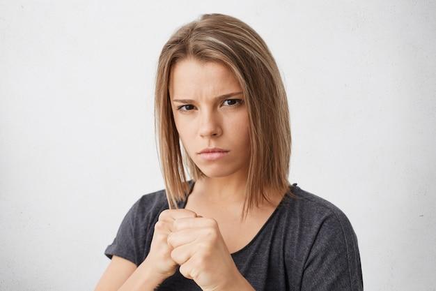 Agressieve jonge vrouw houdt haar vuisten klaar om te vechten en zichzelf te verdedigen tegen onrecht of geweld. sterke vrouw balde vuisten alsof boksen, kijken met ernstige uitdrukking Gratis Foto