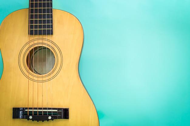 Akoestische gitaar die tegen een groene achtergrond rust Premium Foto