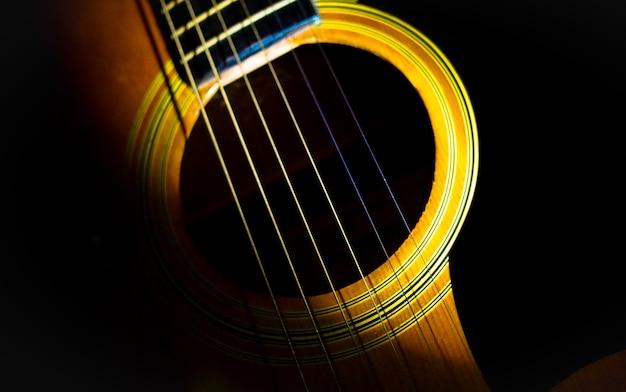 Akoestische gitaar en verlichting op zwarte achtergrond Premium Foto