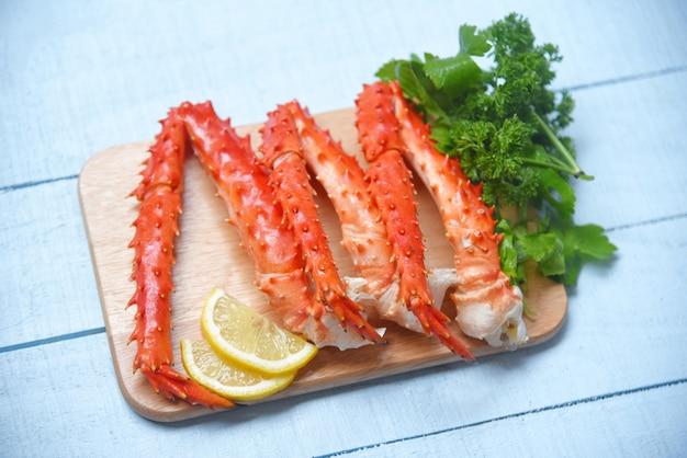 Alaska king crab benen gekookt op houten snijplank met citroen-peterselie - rode krab hokkaido schaal met zeevruchten geserveerd Premium Foto