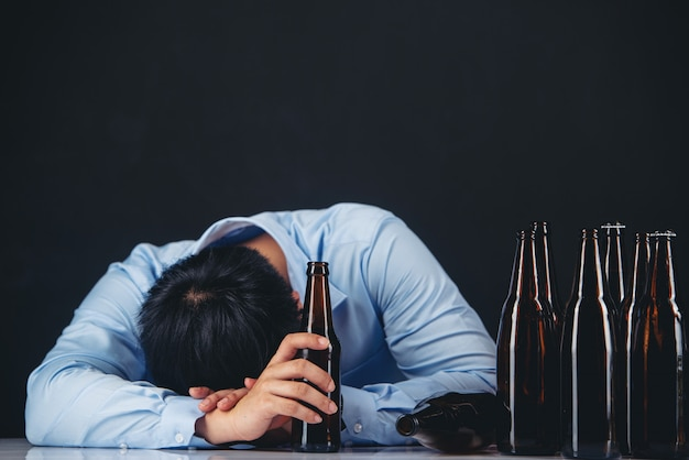 Alcoholische aziatische man met veel bierflessen Gratis Foto