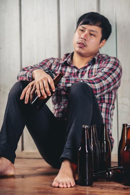Alcoholische aziatische man zit alleen bier drinken Gratis Foto