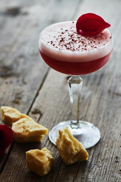 Alcoholische cocktail frambozensaus bestaande uit likeuren, vermout, chocoladeschilfer en citroensap geserveerd in een glazen beker op een houten tafel Premium Foto