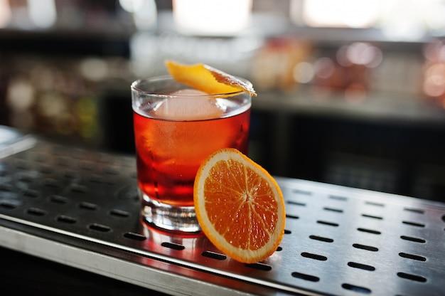 Alcoholische cocktail met ijs en sinaasappel in glas op barlijst Premium Foto