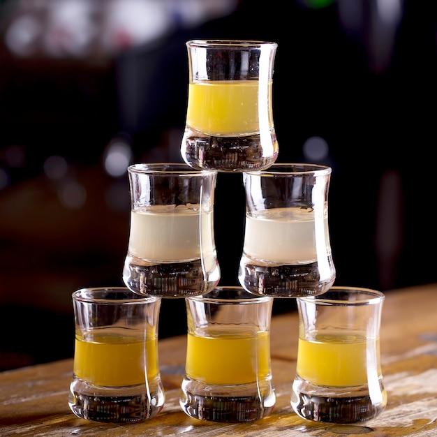 Alcoholische drank in kleine glazen op bar. schoten aan de bartafel. Premium Foto