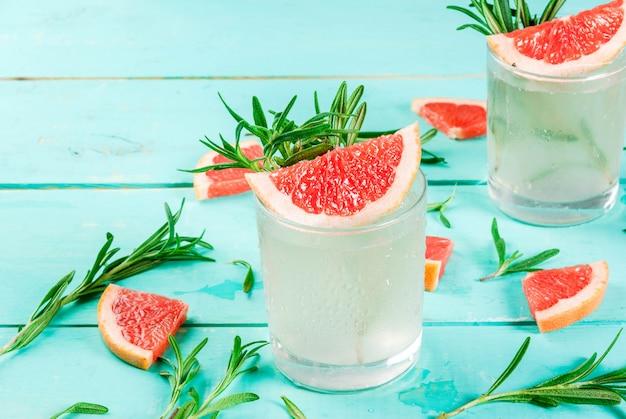 Alcoholische drank, rozemarijn, grapefruit & gin cocktail, op lichtblauwe houten tafel, Premium Foto