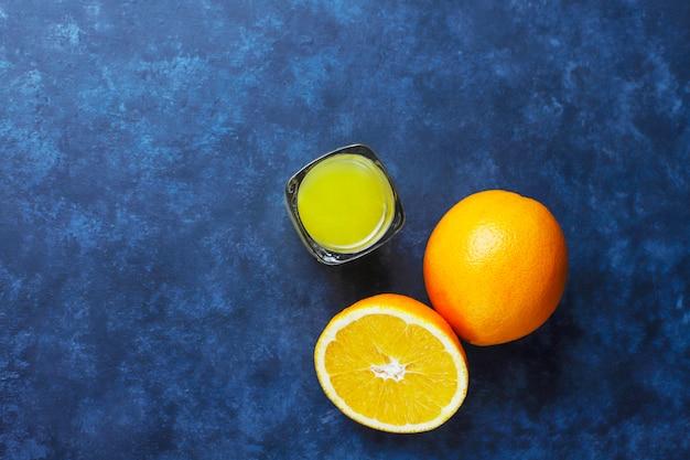 Alcoholische oranje drank in geschoten glas met oranje plak en sinaasappel op donkere achtergrond Gratis Foto