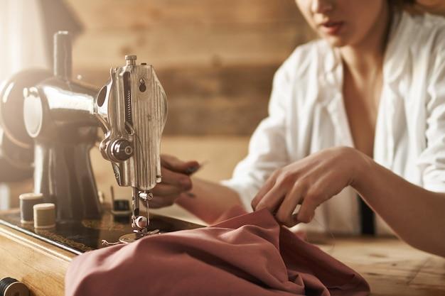 Als je geen kleding kunt kopen, naai er dan een. bijgesneden schot van vrouwelijke kledingstuk maken op naaimachine, het creëren van nieuwe jurk in de werkplaats, wordt geconcentreerd en geconcentreerd. nieuwe naaister die op tijd klaar is met werken Gratis Foto