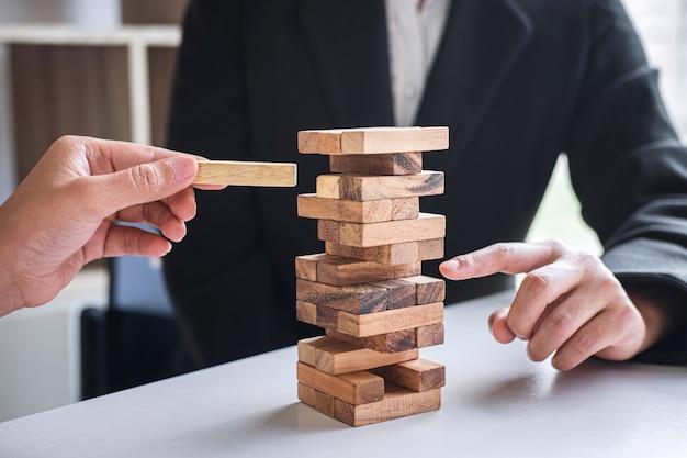 Alternatief risico en strategie in het bedrijfsleven, hand van zakelijk team coöperatief gokken plaatsen van houten blokhiërarchie op de toren om planning en ontwikkeling tot samenwerking succesvol te maken Premium Foto