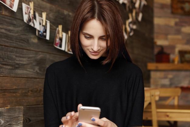 Altijd in contact. moderne aantrekkelijke jonge vrouw met chocolade haar foto's bewerken met behulp van online apps op de mobiele telefoon, kijken naar het scherm met een gelukkige glimlach, messaging Gratis Foto