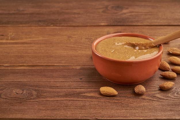 Amandelboter, rauwe voedselpasta gemaakt van vermalen amandelen in notenboter, knapperig en roer Premium Foto