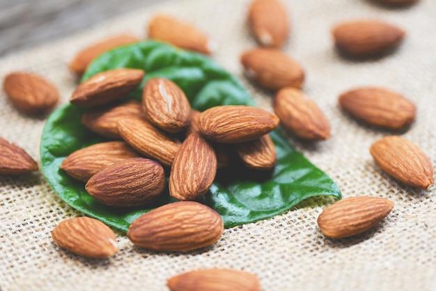 Amandelen op groen blad / close-up natuurlijk eiwitvoedsel van amandelnoten en voor snack op zak Premium Foto