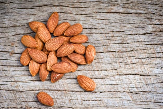 Amandelen op rustieke houten hoogste mening als achtergrond - sluit omhoog natuurlijk proteïnevoedsel van amandelnoten en voor snack Premium Foto