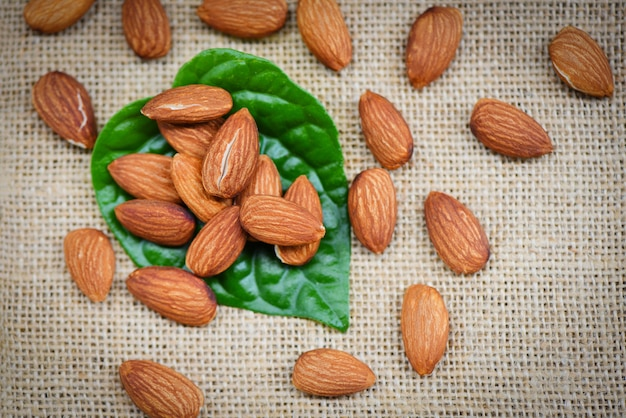 Amandelen op zakachtergrond met groen blad - sluit omhoog natuurlijk de proteïnevoedsel van amandelnoten en voor snack Premium Foto