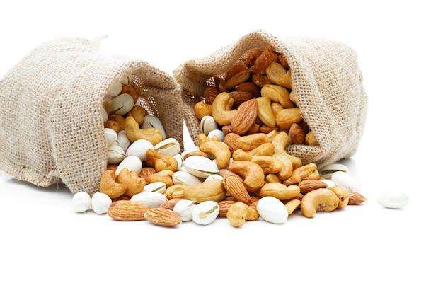 Amandelen pistache en cashewnoten in een zak op een geïsoleerd wit Premium Foto