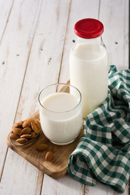 Amandelmelk in glas en fles op witte houten lijst Premium Foto