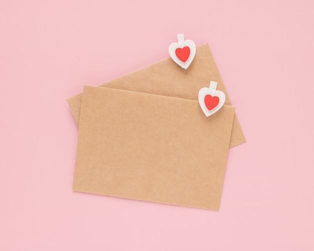 Ambachtelijke enveloppen en houten clips hartjes op een roze achtergrond. valentijnsdag concept. Premium Foto