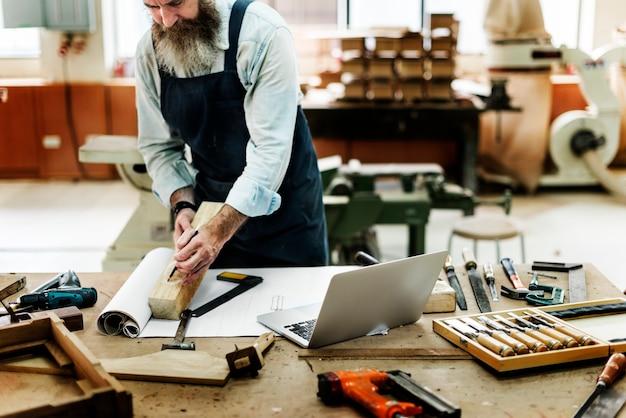 Ambachtsman die in een houten winkel werkt Gratis Foto