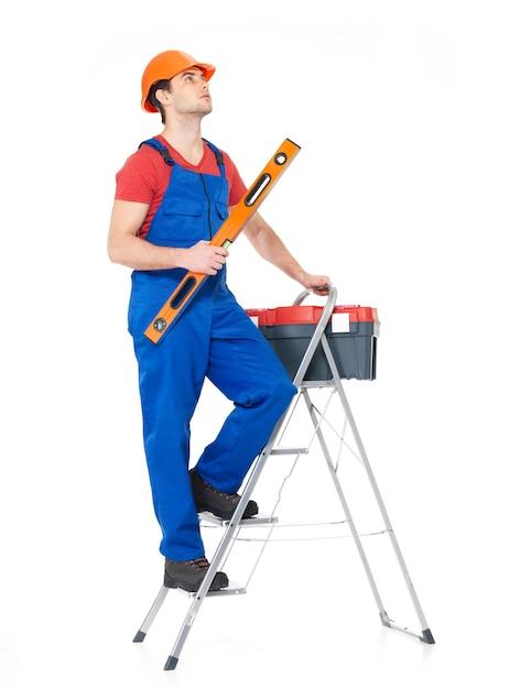 Ambachtsman met tools met trappen, volledig portret op wit Gratis Foto