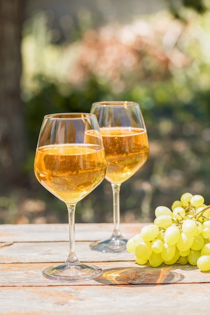Amberwijn in glazen over de aard: stilleven met kaas, druiven en wijn in een rustieke stijl. georgische nationale wijn of italiaanse wijn passito Premium Foto