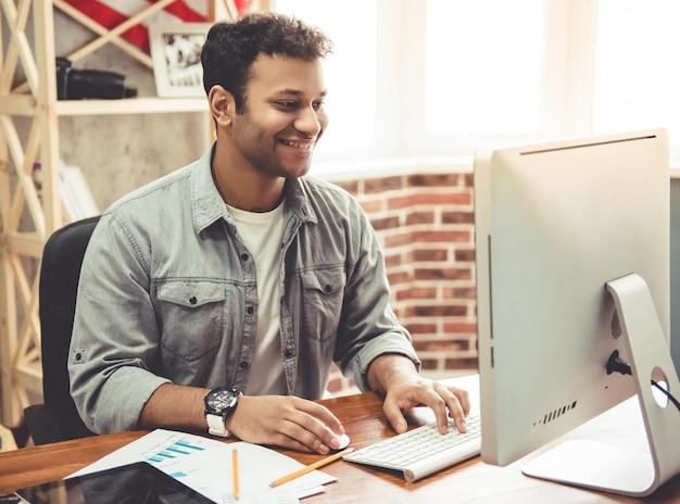 American lacht tijdens het werken met een computer. Premium Foto