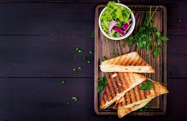 Amerikaans broodje warme kaas. zelfgemaakte gegrilde kaas sandwich voor het ontbijt. bovenaanzicht achtergrond copyspace Premium Foto