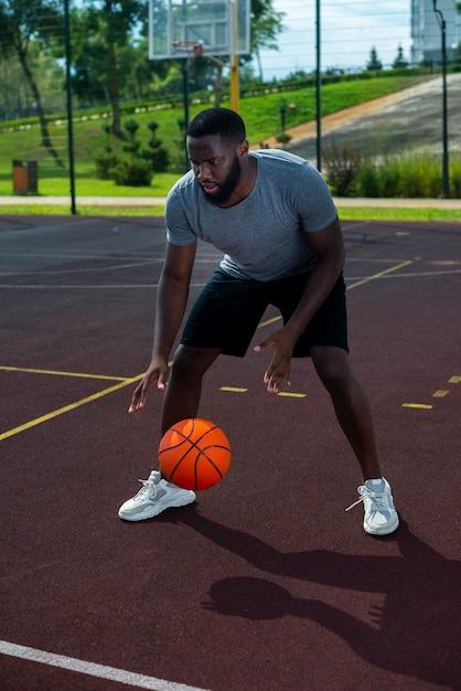Amerikaans knap lang schot van het mensen speelbasketbal Gratis Foto