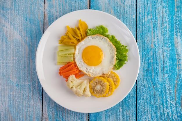 Amerikaans ontbijt op een blauwe tafel met gebakken ei, salade, pompoen, komkommer, wortel, maïs, bloemkool en tomaat. Gratis Foto
