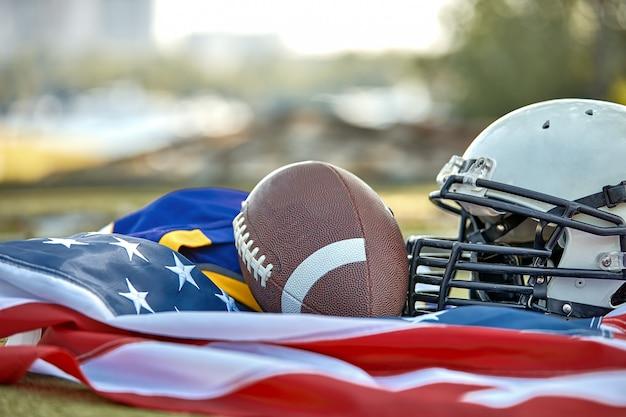 Amerikaans voetbal. amerikaans voetbalmateriaal, helm, balclose-up op van de amerikaanse vlag. patriottisme. Premium Foto