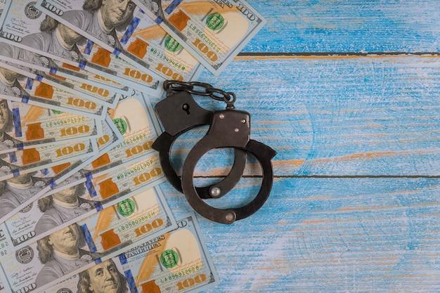 Amerikaanse dollar bankbiljetten geld contant corruptie, vies geld financiële misdaad van handboeien met metalen politie Premium Foto