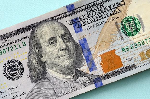 Amerikaanse dollarbiljetten van een nieuw ontwerp met een blauwe streep in het midden zijn leugens op een lichtblauw Premium Foto