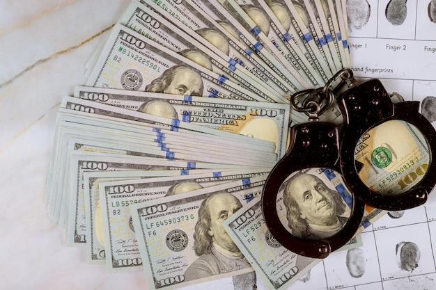 Amerikaanse dollars bankbiljetten criminele vingerafdruk handboeien in de arrestatie corruptie Premium Foto