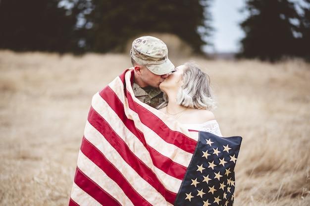 Amerikaanse soldaat kuste zijn liefhebbende vrouw terwijl ze gewikkeld was in een amerikaanse vlag Gratis Foto