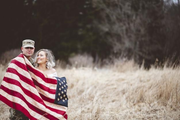 Amerikaanse soldaat met zijn glimlachende vrouw gehuld in een amerikaanse vlag Gratis Foto