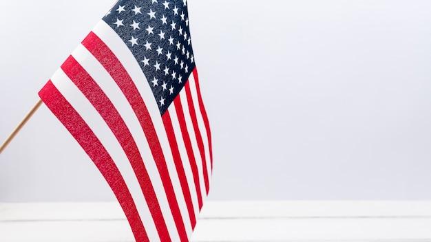 Amerikaanse vlag die tegen witte muur in studio golven Gratis Foto