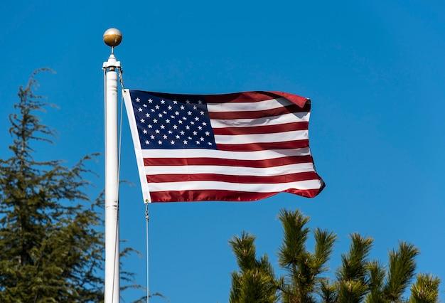 Amerikaanse vlag zwaaien tegen blauwe hemel, verenigde staten vlag zwaaien Premium Foto