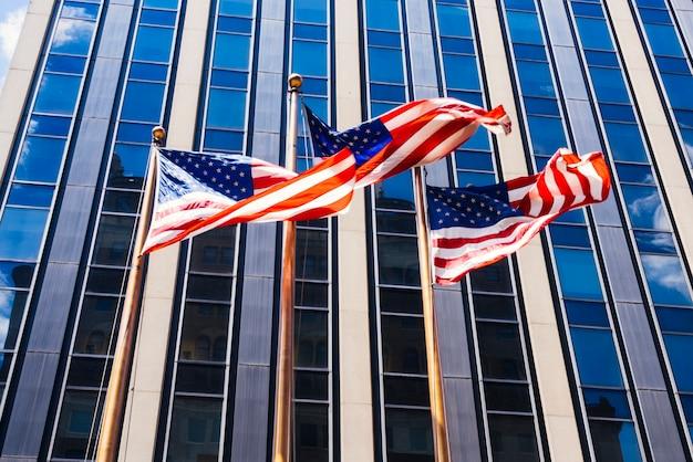 Amerikaanse vlaggen die op glazige de bouwachtergrond golven Gratis Foto