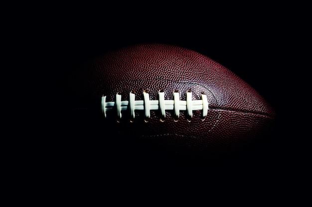 Amerikaanse voetbalbal die op zwarte ruimte wordt geïsoleerd Premium Foto
